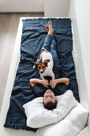 Happy young boy with a dog in a cozy interior.