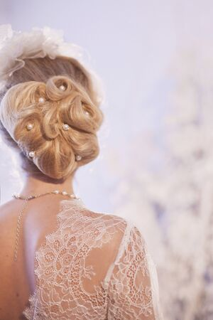 An unrecognizable bride in a lace dress with a beautiful hairstyle with her back to the camera. Selective focus.