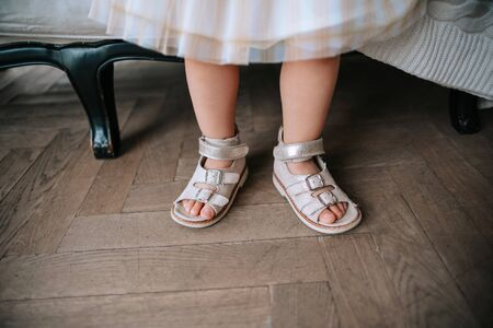 An unrecognizable little girl in pink sandals. Stock Photo
