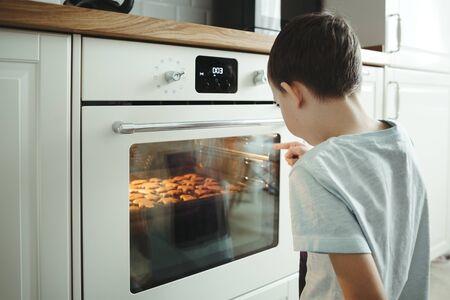 Un giovane ragazzo cucina i biscotti e aspetta pazientemente accanto a un forno sicuro all'interno della casa.