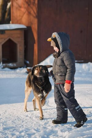 Small children in winter clothes with dog outdoors.