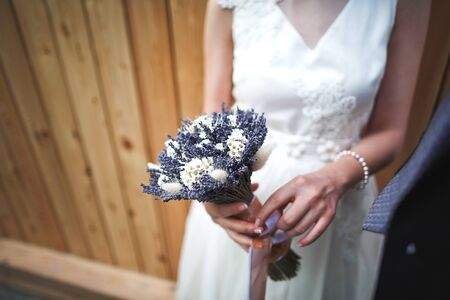 Selective focus unusual bouquet of wild flowers chamomile, lavender, ears in the hands of an crop bride in a white wedding dress.