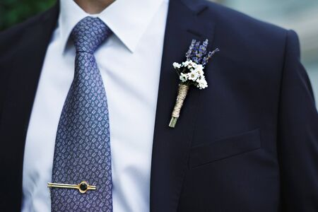 Boutonniere of unusual flowers on the grooms jacket.