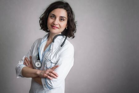 Cute smiling woman in white medical gown stands against a gray wall and looks at the camera. On the neck of a stethoscope. Stok Fotoğraf