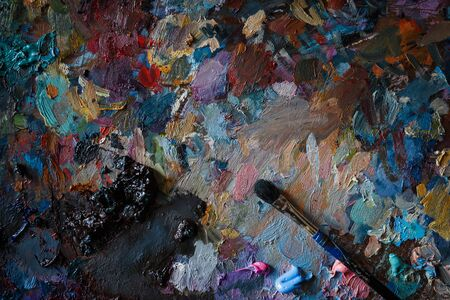 Artists palette with multi-colored smeared colors and one brush. Close up.