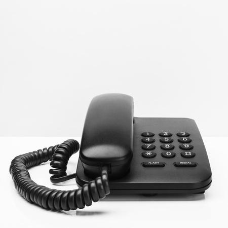 Old office desktop phone on white desk