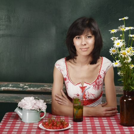 Outdoor portrait of young woman sitting at table in garden