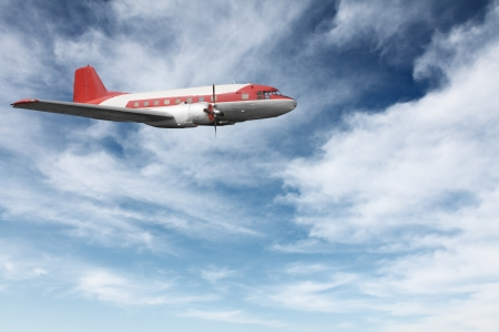 Old airplane flying against blue sky Stock Photo