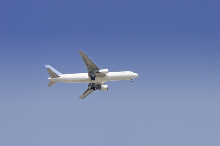 Airliner flying in blue cloudless sky at sunny day