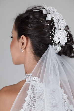 wedding hairstyle: Young beautiful bride in wedding dress and luxury coiffure