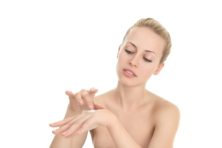 Young woman applying moistyring cream on hands
