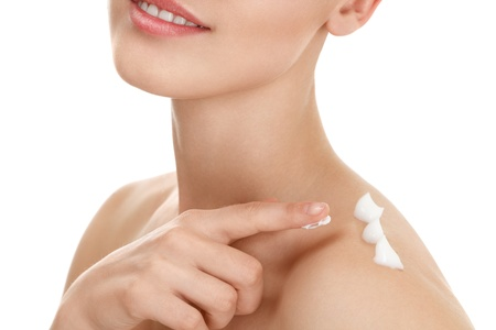 Young woman applying moistyring cream on skin Stock Photo
