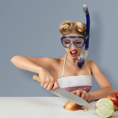 chopping board: Young blonde woman cutting onion in diving scuba mask for protect eyes