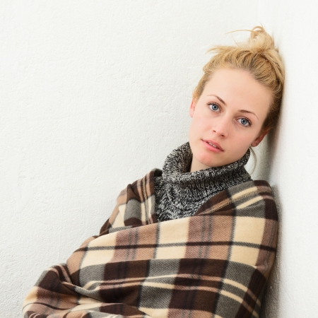 Young blonde woman wrapped in a blanket Stock Photo