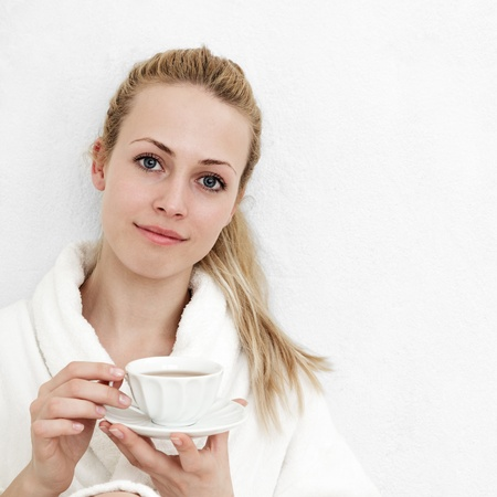 Beautiful blonde woman with tea against room wall Stock Photo - 15408340
