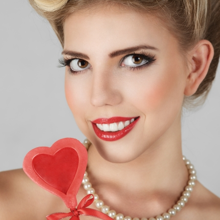 Beautiful blonde young woman with bright make-up and candy studio portrait