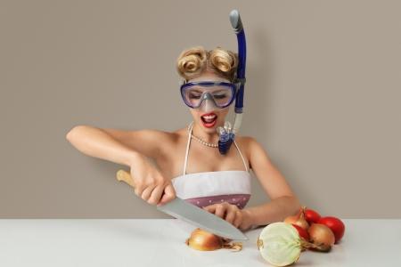 mascara de gas: Mujer joven rubia cortar la cebolla en la máscara de buceo para proteger los ojos