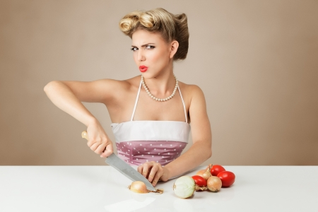 Young blonde woman cutting onion in kitchen Stock Photo