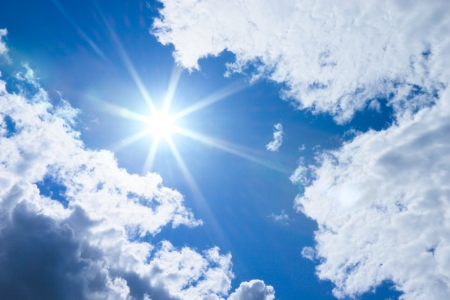 Bright summer sun and clouds on blue sky