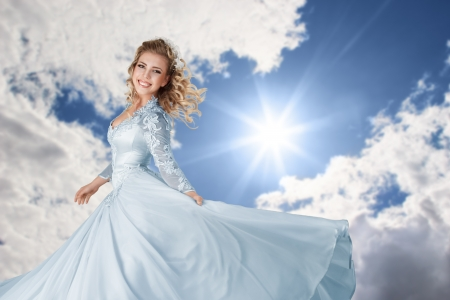 Happy young bride in long beautiful dress against blue bright sunny sky Stock Photo