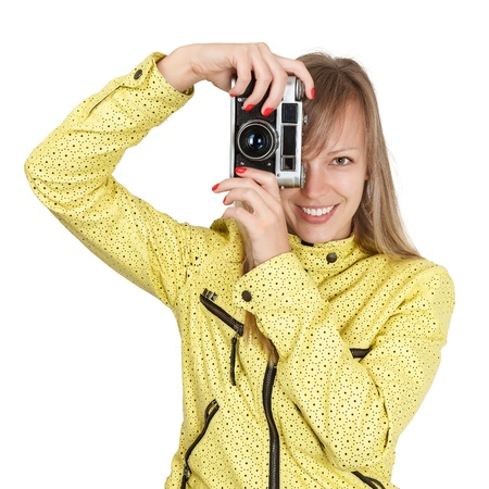 Young blonde woman photohrapher shooting with retro film camera isolated on white background photo