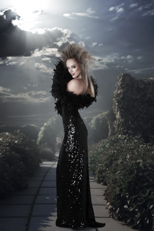Elegant woman in long black dress at mystic garden