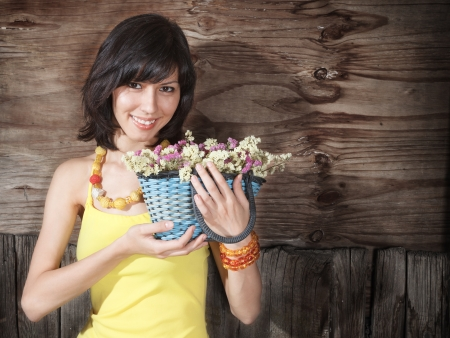 Beautiful young woman with flowers bouquet in yellow dress outdoor portrait against wooden wall