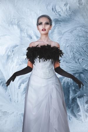 winter garden: Elegant woman in long white dress at mystic winter garden Stock Photo