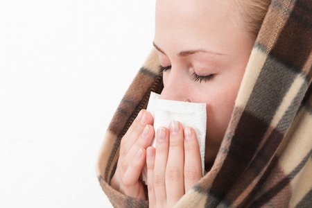 A woman with a symptoms cold flu allergy wiping or blowing her nose Stock Photo - 16522832