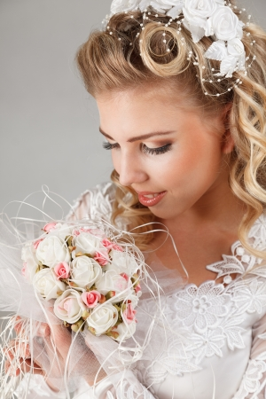 Young bride in white wedding dress happy smiling with bouquet in hands Stock Photo