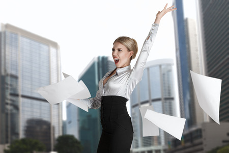 Young businesswoman throws paper document pages in front of cityscape