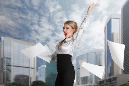 throw paper: Young businesswoman throws paper document pages in front of cityscape
