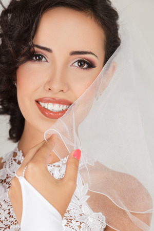 Young bride in white wedding dress with beautiful hairstyle