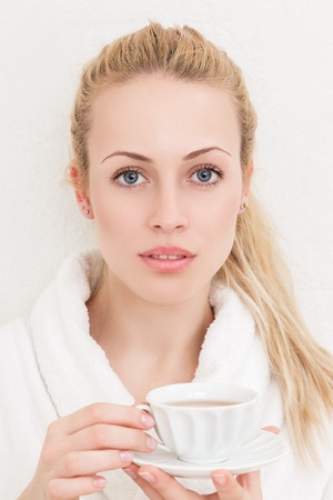 sidewards: Young beautiful woman with tea cup indoor portrait Stock Photo