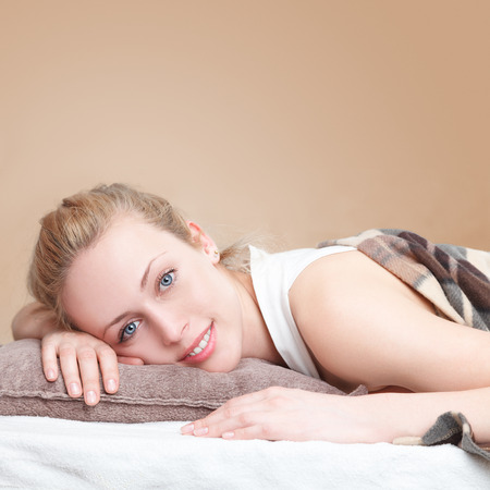 Young beautiful woman lying down on a bed in bedroom photo