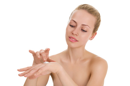 Young woman applying moistyring cream on hands photo