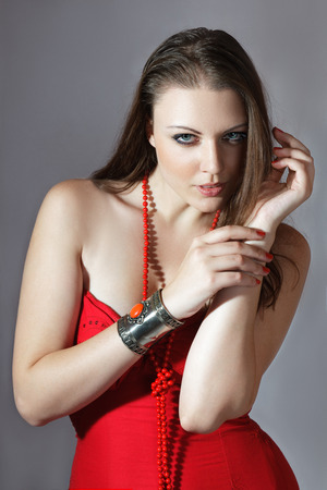 Beautiful young woman in red dress fashion studio shot