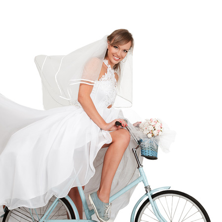 Happy young bride in long beautiful dress cycling on vintage bicycle