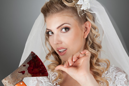Beautiful young bride with bloody ax in hands studio indoor portrait