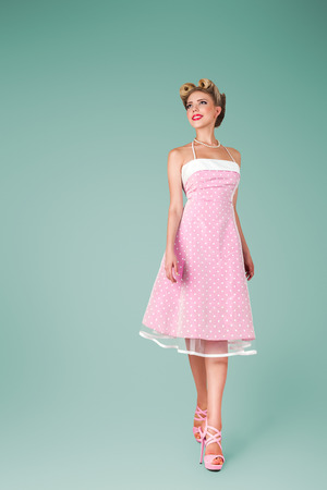Young woman with beautiful hairstyle in pink vintage dress