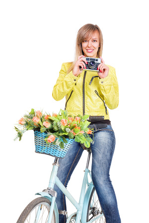 Young woman on bicycle take photo with vintage film camera isolated over white backgrounc