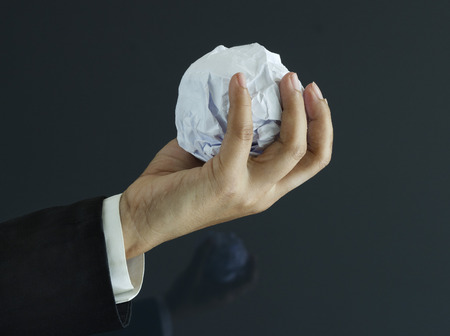 bisiness: Ball of paper in hand on dark background, business concept Stock Photo