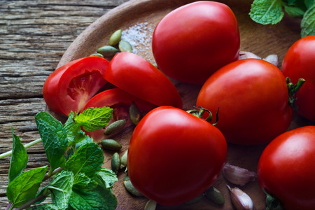 biologic: Tomato and ingredient in wood plate on wooden table