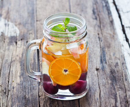 fruit in water: mug delicious refreshing drink of mix fruits with mint on wooden infusioned water Stock Photo