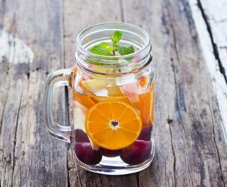 frutas: taza deliciosa bebida refrescante mezcla de frutas con menta en agua infusioned madera Foto de archivo