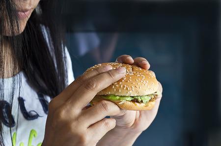 comida chatarra: Las mujeres ven la hamburguesa en la mano sobre fondo oscuro concepto de comida chatarra