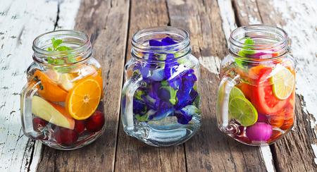 나무 배경에 세 잔 맛 상쾌한 혼합 과일 음료와 허브