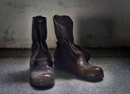 muddy clothes: Dirty old brown boots over blue grunge background Stock Photo