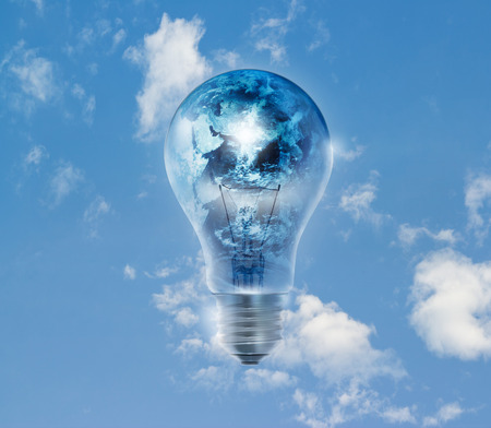 Earth globe and storm in the light bulb on a blue sky vibrant background Environment concept Earth photo