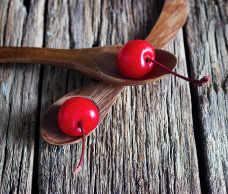 maraschino cherry vibrant on wooden spoon and old table background Stock Photo